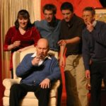 five actors, one in a chair all pointing