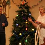 two actors in front of a xmas tree